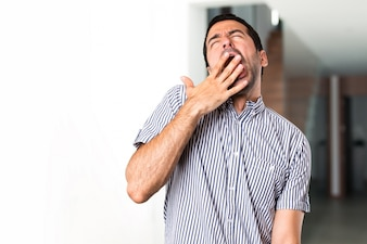Красивый мужчина зевает внутри дома