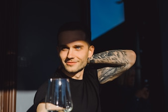 Handsome tattooed man on a summer terrace in a city cafe is drinking wine. Street Cafe.