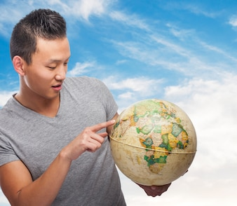 Handsome young asian man indicating some location on a globe