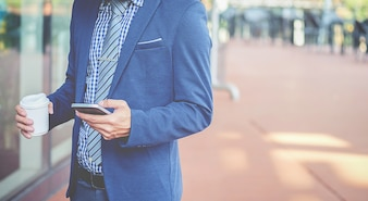 彼のスマートフォンを使って、ハンサムな若い実業家。