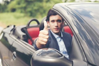 Handsome young man in sports car wearing suit.