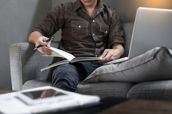 Handsome Young Man Sitting on the Living Room Couch, Casual young man reading documents on sofa at home