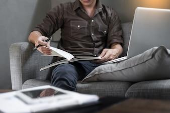 リラックスルームのソファに座っているハンサムな若い男、自宅でソファの文書を読むカジュアルな若い男