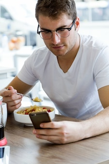 Handsome young man using his mobile phone while enjoying the breakfast in the kitchen.