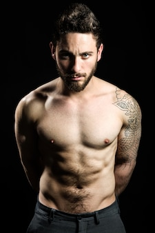 Handsome young man with tattoos posing. Isolated on black.