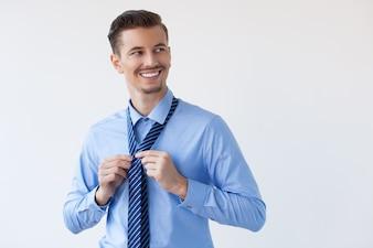 Happy Attractive Elegant Young Man Tying Necktie