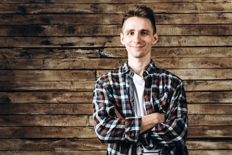 Happy attractive young man in plaid shirt standing and smiling over wooden background