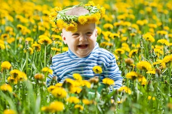 Happy baby in flowers meadow