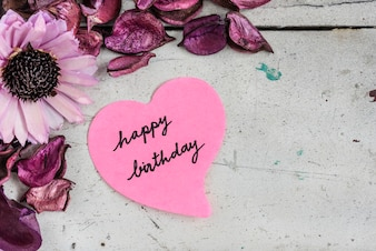 Happy birthday note in heart shape paper with pink flowers