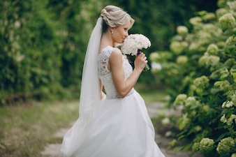 Happy bride smelling her bouquet of white roses