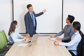 Happy business coach consulting team in boardroom