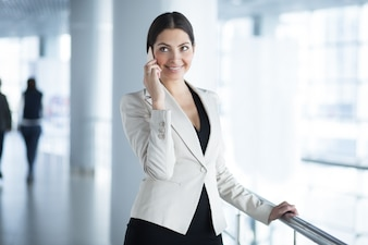 Happy Business Woman Calling on Phone in Hall