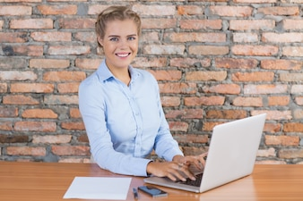 Happy Business Woman Working on Laptop at Desk