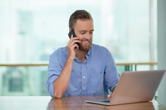 Happy businessman talking on the phone to client