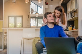 Happy couple doing business together working at small office at home, Portrait of a cheerful woman hugging man from behind