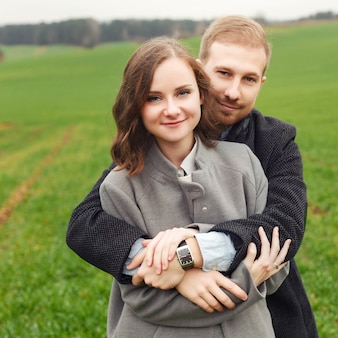 Happy couple hugging in the field