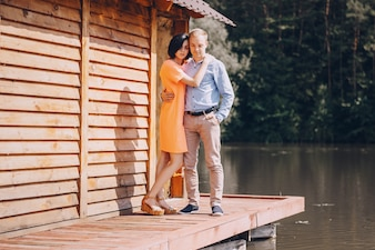 Happy couple next to a wooden hut