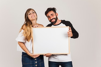 Happy couple presenting board
