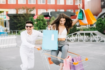 Happy couple riding shopping cart