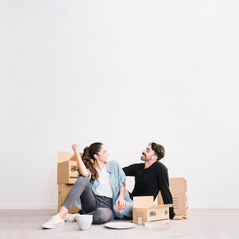 Happy couple sitting in front of moving boxes
