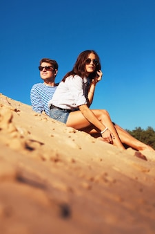 Happy couple wearing sunglasses and sitting on the sand