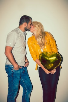 Happy couple with balloon kissing