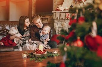 正面に焦点外のクリスマスツリーとソファに座って幸せな家族