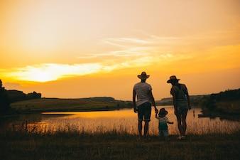 幸せな家族一緒に、両親は日没時に小さな子供と一緒に。父は空中で赤ちゃんを上げる。