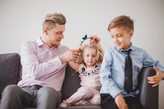 Happy father with his children on the couch