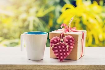 ハッピーファストルの日コンセプトコーヒーカップとギフトボックスと心の木製テーブルに日光。