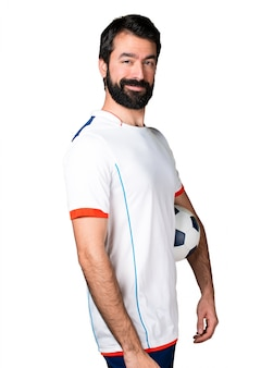 Happy football player holding a soccer ball