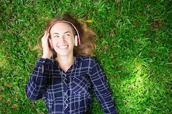 Happy Girl Enjoying Listening to Music on Grass