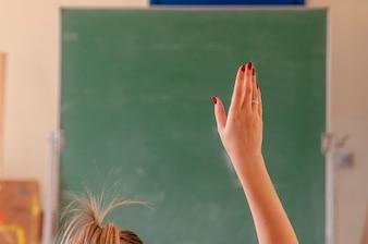 Happy girl raised hands in classroom