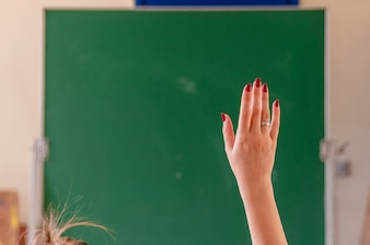Happy girl raised hands in classroom