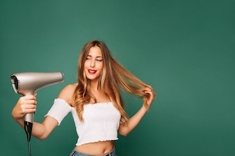Happy girl with hairdryer