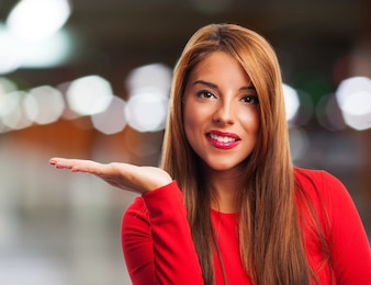 Happy girl with open hand palm on blurred background