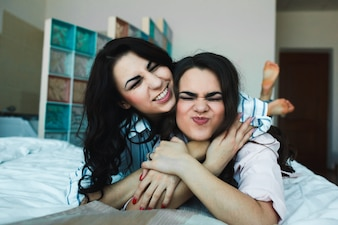 Happy girls posing on bed