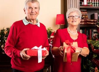 Happy grandparents holding christmas presents