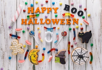 Happy Halloween caption with candies and cookies
