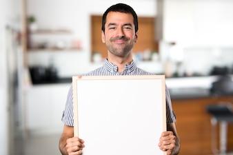 Happy Handsome man holding an empty placard inside house