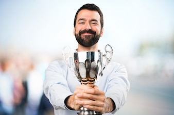 Happy Handsome man with beard holding a trophy on unfocused background