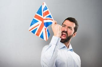 幸せなハンサムな男は、ひげを備えた英国の旗を身に着けている背景に