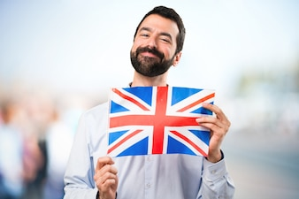 Happy Handsome man with beard holding an United Kingdom flag on unfocused background