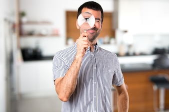Happy Handsome man  with magnifying glass inside house