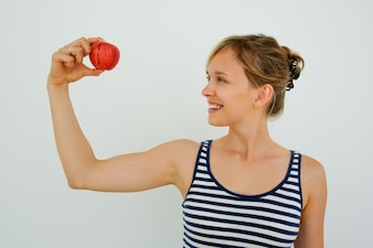 Happy healthy woman looking at apple