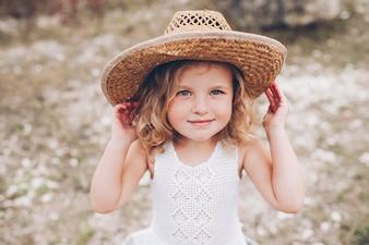 Happy little girl wearing a hat outdoors
