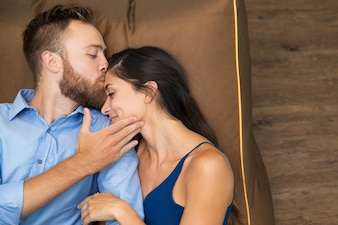 Happy man kissing his wife when lying on sofa