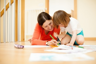 Happy mother and child sketching   at parquet floor