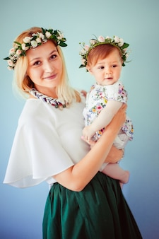 Happy mother and daughter dressed in fancy style pose for the camera