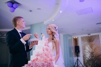 Happy newlyweds eating wedding cake